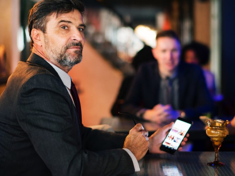 a man in a business suit sitting at bar with his cell phone