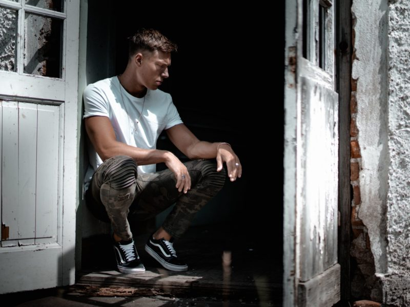 a man sitting in a darkened doorway appearing to be ashamed